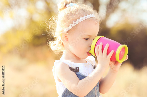 Young Baby 2 3 Year Old Girl Drinking With Plastic Cup Outdoors Wearing Stylish