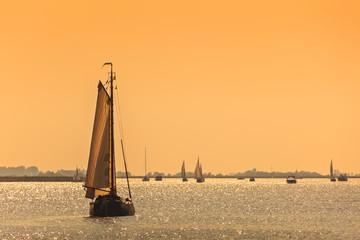 Frisian Dutch sailing ships during sundown