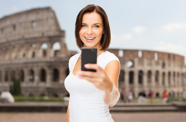woman taking selfie with smartphone over coliseum