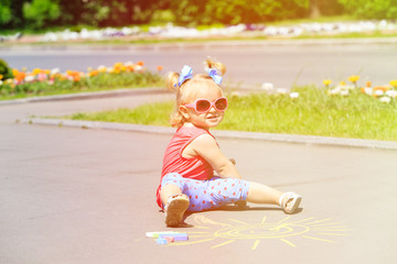 little girl drawing sun with chalks on a street