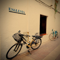 two bicycles at a white wall