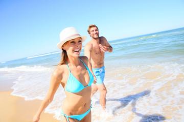 Couple having fun running on the beach