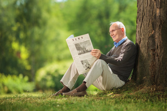 Senior gentleman reading a newspaper in park