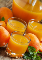 Fresh apricot juice and apricots with mint on old wooden table,