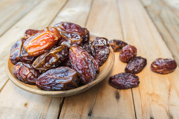 Dates fruit in a wooden bowl closeup on wooden background