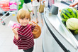Little boy buying fruits in a food store