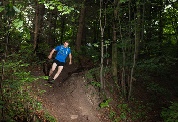 single man in the blue t-shirt running down the hard track in the forest