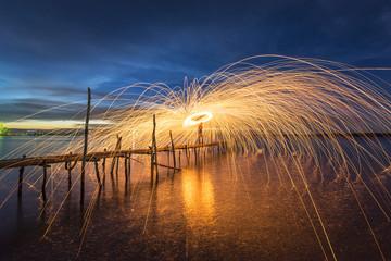 Amazing Fire dancing steel wool coast the sea on bamboo bridge in the twilight.