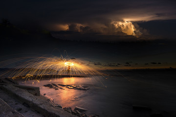 Amazing Fire dancing steel wool coast the sea there is lightning in the background