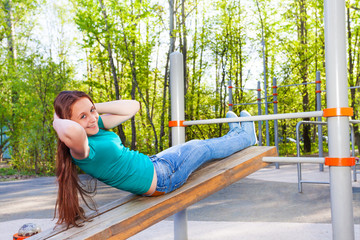 Girl does curls up on the wooden board outside
