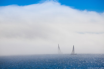 Lonely sailboats in the morning mist