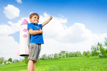 Boy wears paper rocket toy and holds arm up