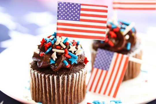 4th of July cupcakes with American flag background, shallow depth of field