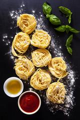 Preparation of homemade spaghetti. tomato sauce, basil and olive