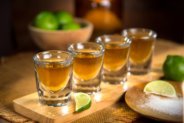 Four shot glasses with tequila bottle and bowl of limes with salt at a bar