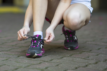 Young woman is tying the laces before running. Close-up, running, healthy lifestyle.