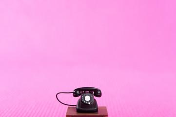 ピンクの背景と黒電話