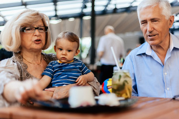 Grandparents With Their Grandson At Cafe