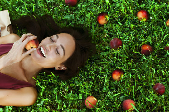 Beautiful happy young woman smiling eating a peach