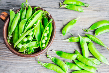 green peas in pods young on gray wooden background, rustic,