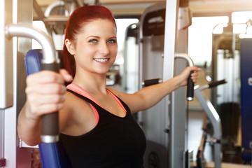 lachende Frau trainiert im Fitnessstudio