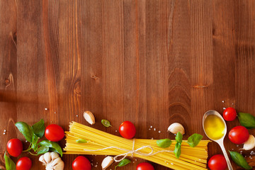 Uncooked spaghetti, cherry tomato, basil, garlic and olive oil, ingredients for cooking pasta