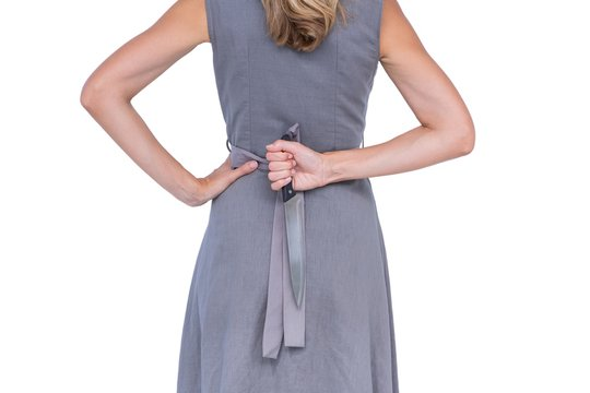 Wear view of woman hiding knife behind her back