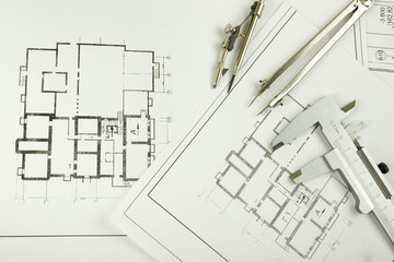 Architectural project, blueprints, blueprint rolls and divider compass, calipers, folding ruler on plans Engineering tools view from the top. Copy space. Construction background.