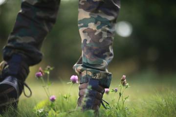 a man walking in the field feet grass flowers macro