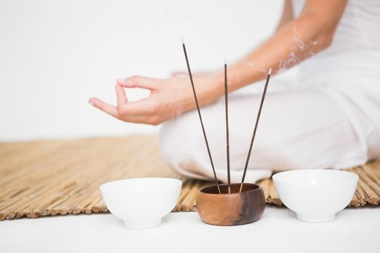 Fit woman meditating on bamboo mat
