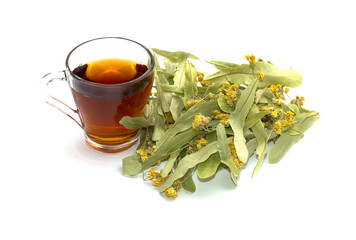 mug of lime tea and heap of a collected linden on a white backgr
