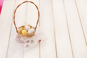 Basket with eggs on white picnic table/Pink background. Easter eggs in basket.