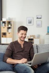 lächelnder mann mit laptop auf dem sofa
