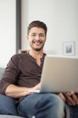 zufriedener mann mit laptop zu hause