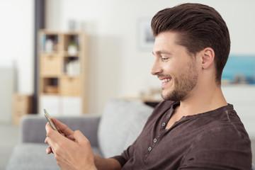 lächelnder mann zu hause schaut auf sein smartphone