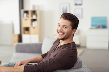lachender mann zu hause auf dem sofa