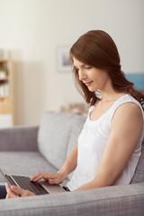 junge frau sitzt auf dem sofa und schaut auf laptop