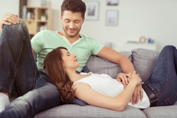 junges paar liegt entspannt auf dem sofa