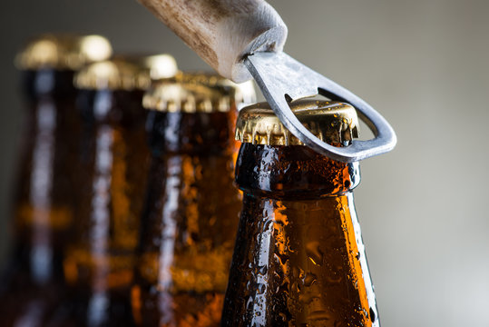 Brown ice cold beer bottles with old opener