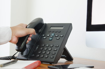 hand hold a telephone in the office for contact customer support