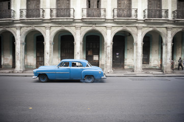 Old American car drives in front of the traditional architecture of a colonial arcade
