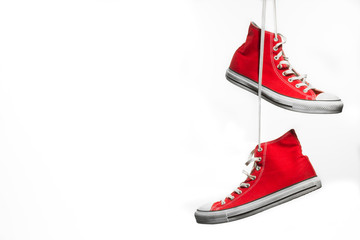 Red sneakers hanging in front of a white background