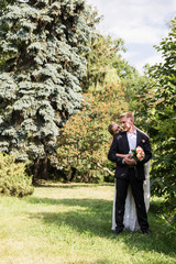 Portrait of a newlywed couple standing embracing