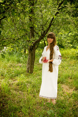 young girl in the Ukrainian embroidered shirt, standing barefoot