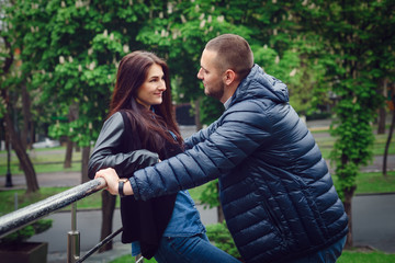 Beautiful young couple in love on a date outdoors on modern urban background. Smiling and hugging. Bearded handsome man and brunette pretty woman in casual dress.