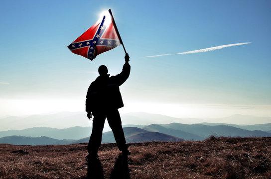 successfull silhouette man winner waving Confederate flag on top of the mountain peak