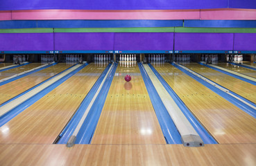 Generic Bowling Alley lanes with bowling ball going towards the pins