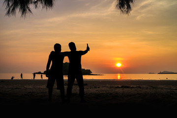 Silhouette Two young men on the beach having party, drinking and