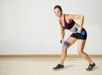 Full length photo of a beautiful, smiling fitness woman lifting weights during a workout. Indoor on a white background