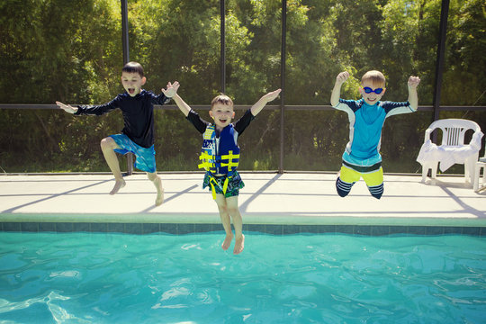 Cute young boys jumping into a swimming pool while on a fun vacation